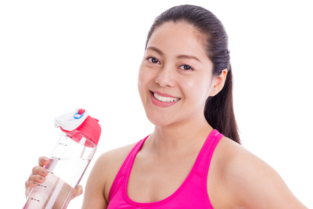 Beautiful young fitness woman happy smiling holding water bottle. Healthy lifestyle photo of Asian fitness model isolated on white background. photo