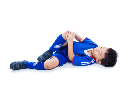 Sports injury. Youth asian (thai) soccer player in blue uniform with pain in knee. Isolated on white background. Studio shot. Full body. Boy lie down. Stockfoto