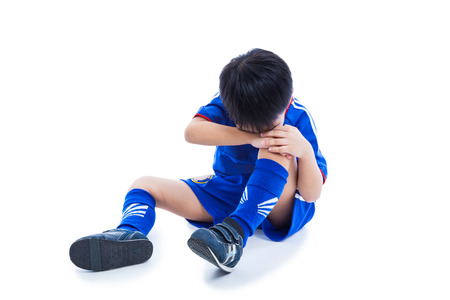 Sports injury. Youth asian (thai) soccer player in blue uniform with pain in knee. Isolated on white background. Studio shot. Full body. Boy sitting and crying.