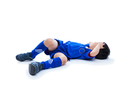 Sports injury. Youth asian (thai) soccer player in blue uniform with black eye on left. Isolated on white background. Studio shot. Full body. Boy lie down. Stock Photo