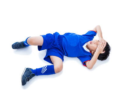 injurious: Sports injury. Youth asian (thai) soccer player in blue uniform painful. Child closed eyes and touching his forehead. Isolated on white background. Studio shot. Boy lie down. Top view. Full body.