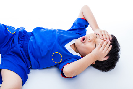 Sports injury. Youth asian (thai) soccer player in blue uniform painful. Child closed eyes and touching his forehead. On white background. Studio shot. Boy lie down. Top view Фото со стока