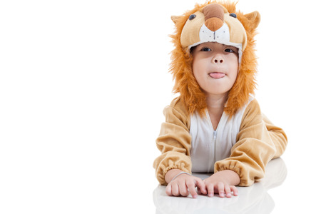 Little lovely asian boy trick or treat concept, lovely boy costumed and acting like a lion, stick out tongue and free form copy space. Isolated on white background. Studio shoot