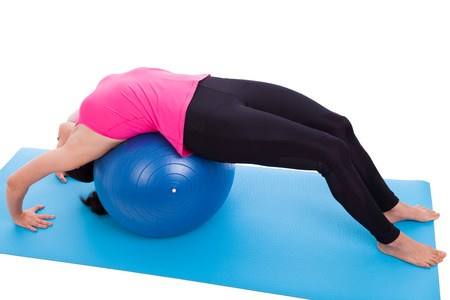 pilates studio: Athletic woman doing yoga or pilates training, young lady lies on blue gym ball (urdhva dhanurasana) as part of muscles building training exercise. Isolated on white background. Studio shot. Full body