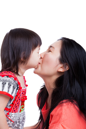 smooching: Happy family - Mother and little asian girl kissing together, on white background. Mothers Day celebration Stock Photo