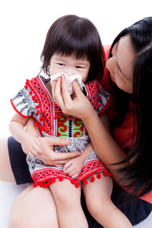 mum and child: Asian mother wipes snot her daughter. Little girl with allergy symptom and sitting on young woman lap. On white background