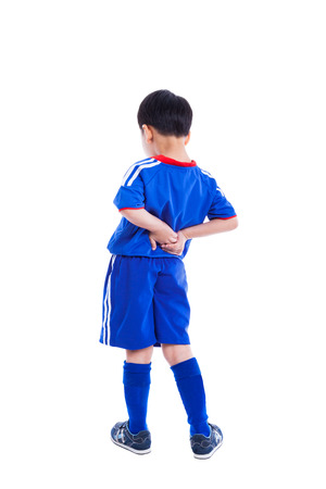 youth background: Back pain. Athlete little asian (thai) boy in blue sportswear standing and rubbing the muscles of his lower back, isolated on white background. Studio shot