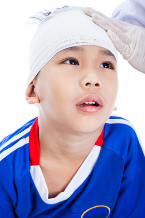 injurious: Athlete little asian (thai) boy in blue sportswear with trauma of the head. Doctor makes a bandage on head patient. Child unhappy, on white background