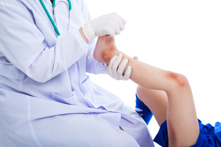 bruised: Doctor examining a patient suffering from injured on leg  with a bruise. Sport injury. Professional checking ankle injury athlete, on white background. Studio shot