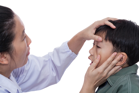 Little asian boy with an injured left eye. Doctor examining and first aid a patient. Child pain. Studio shot. On white background