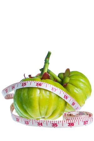 hierbas: Todav�a vida arcinia atroviridis fruta fresca con la cinta de medici�n, aislada en el fondo blanco. tailand�s de la hierba y un mont�n de sabor amargo de la vitamina C para una buena salud. Extraer como un producto de la p�rdida de peso.