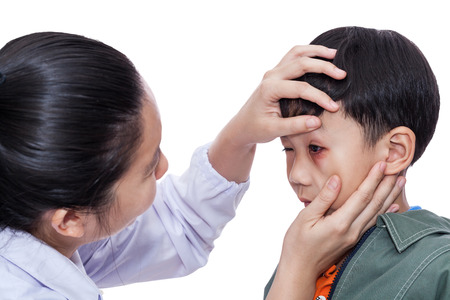 injurious: Little asian boy with an injured eye. Doctor examining and first aid a patient injured on left eye bruise. Studio shot. On white background