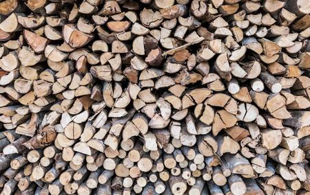 kindling: Close up stack of firewood, wood background texture. Layer of stored cut timber.