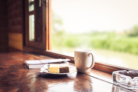 Cake and a cup of coffee on wooden table near window sill. Blurred nature background. Time with snacks concept. Shallow depth of field DOF dessert in focus. Window with sunbeam shining Stok Fotoğraf