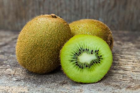 fresh taste: Close up fresh kiwi fruit on old wood background. Kiwi fruit is sweet and sour taste, nutritive value and high-fiber.