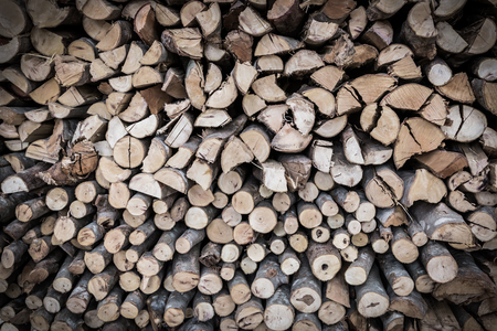 stored: Close up stack of firewood, wood background texture. Layer of stored cut timber. Low key picture style.