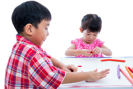 strengthen: Little asian children playing and creating toys from play dough on table, on white background. Strengthen the imagination of child