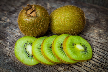 green backgrounds: Close up fresh kiwi fruit on old wood background. Kiwi fruit is sweet and sour taste, nutritive value and high-fiber. Low key picture style