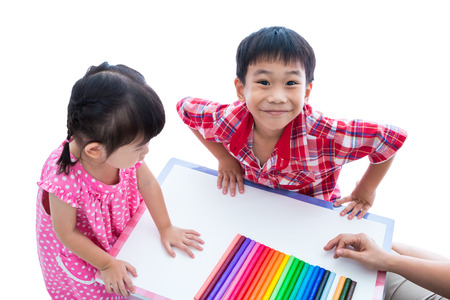 strengthen: Little asian children prepare create toys from play dough on table. Boy smiling and looking at camera, on white background. Strengthen the imagination of child Stock Photo