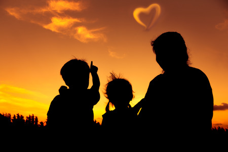 Silhouette of mother and two kids sitting and looking sky at sunset. Little boy point to heart-shape clouds. Colorful sky background orange and gold colors sunset sky. Friendly family. Banque d'images