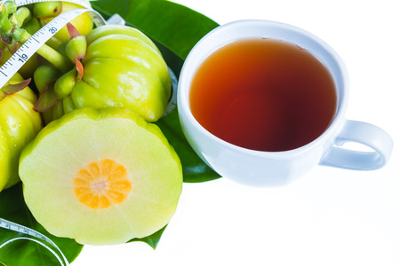 Still life arcinia atroviridis fresh fruit with measuring tape on leaves and a cup of tea, on white background. Thai herb, sour flavor lots of vitamin C for good health. Diet healthcare weight reduction concept Stock Photo