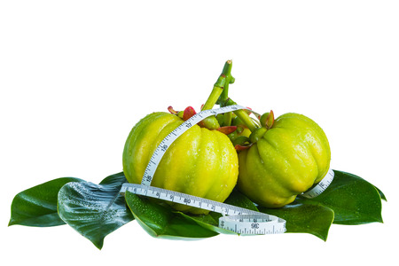 Still life arcinia atroviridis fresh fruit with measuring tape on leaves, isolated on white background. Thai herb, sour flavor lots of vitamin C for good health. Diet healthcare weight reduction concept Banque d'images