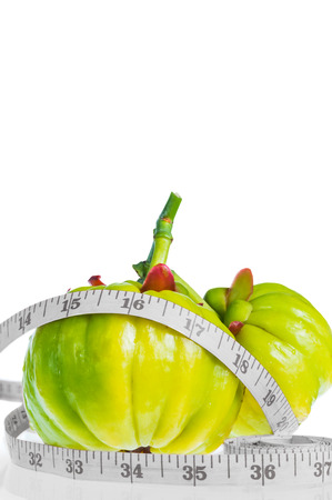 tartaric: Still life garcinia atroviridis fresh fruit with measuring tape and free form copy space, isolated on white background. Thai herb for good health. Diet healthcare weight reduction concept Stock Photo