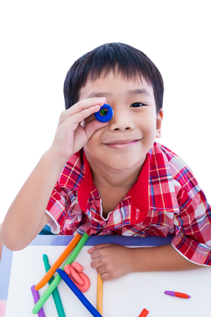 strengthen: Little asian boy playing and creating toys from play dough. Child smiling and show his works from clay, on white background. Strengthen the imagination of child Stock Photo