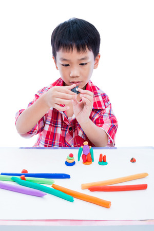 strengthen: Little asian boy playing and creating toys from play dough. Child moulding whale modeling clay, on white background. Strengthen the imagination of child Stock Photo