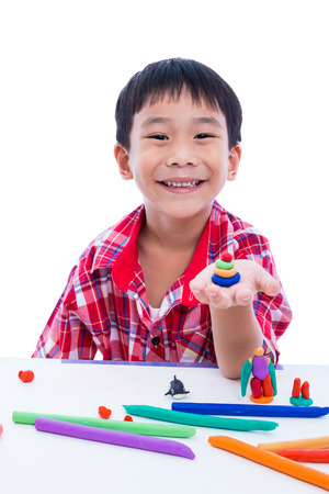 strengthen: Little asian boy playing and creating toys from play dough. Child smiling and show his works from clay on hand, on white background. Strengthen the imagination of child Stock Photo