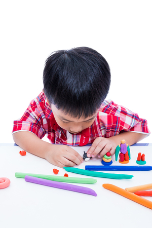 clay modeling: Little asian boy playing and creating toys from play dough. Child moulding whale modeling clay, on white background. Strengthen the imagination of child Stock Photo