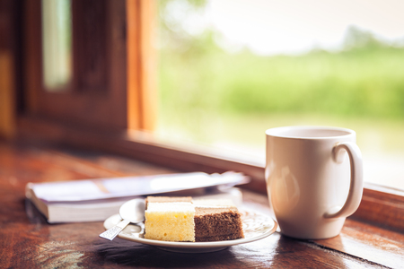 dof: Cake and a cup of coffee on wooden table near window sill. Blurred nature background. Time with snacks concept. Shallow depth of field (DOF) dessert in focus. Window with sunbeam shining Stock Photo