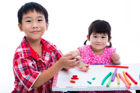 strengthen: Little asian children playing and creating toys from play dough on table. Boy and girl smiling and looking at camera, on white background. Strengthen the imagination of child Stock Photo