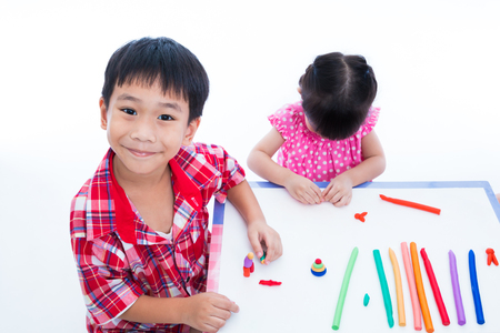 strengthen: Little asian children playing and creating toys from play dough on table. Boy smiling and looking at camera, on white background. Strengthen the imagination of child Stock Photo