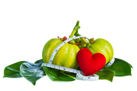 Garcinia atroviridis fruit with measuring tape and red heart-shaped on leaves,isolated on white background. Herb sour flavor lots of vitamin C for good health. Diet healthcare weight reduction concept