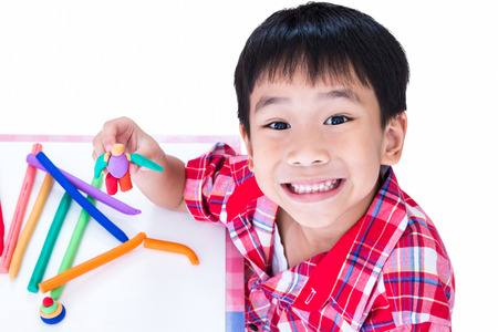 Little asian boy playing and creating toys from play dough. Child smiling and show his works from clay, on white background. Strengthen the imagination of child Banque d'images