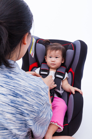seat: Image of Mother fasten with security belt to her little asian (thai) girl in safety car-seat, on white background. Concept about vehicle safety, symbol of protection, care Stock Photo