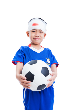holding head: Athlete little asian (thai) boy in blue sportswear with trauma of the head holding a football and crying, bloody on bandage, shoot in studio, Isolated on white background