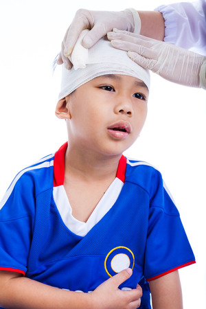 head injury: Sports injury. Athlete little asian (thai) boy in blue sportswear with trauma of the head. Doctor makes a bandage on head patient. Child unhappy, on white background. Studio shoot.