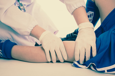 kid at doctor: Sports injury. Youth soccer player in blue uniform with pain in knee. Doctor perform checking and first aid at knee trauma. Studio shot. Cream tones.