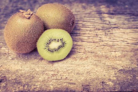 fresh taste: Close up fresh kiwi fruit on old wood background. Kiwi fruit is sweet and sour taste, nutritive value and high-fiber. Vintage picture style. Free form copy space. Stock Photo