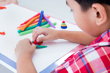 strengthen: Little asian boy playing and creating toys from play dough. Child moulding robot modeling clay. Strengthen the imagination of child