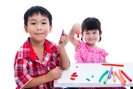 strengthen: Little asian children playing and creating toys from play dough on table. Boy and girl smiling and show works from clay at camera, over white background. Strengthen the imagination of child