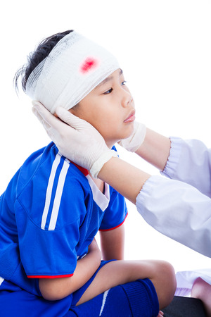 injurious: Sports injury. Athlete little asian (thai) boy in blue sportswear with trauma of the head, bloody on bandage. Doctor makes a bandage on head patient, on white background. Studio shoot. Side view.
