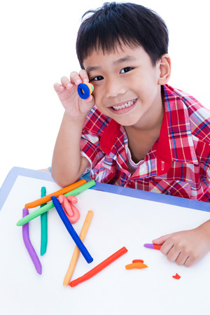 asian art: Little asian boy playing and creating toys from play dough. Child smiling and show his works from clay, over white background. Strengthen the imagination of child