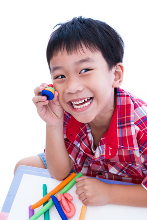 strengthen: Little asian boy playing and creating toys from play dough. Child smiling and show his works from clay, over white background. Strengthen the imagination of child