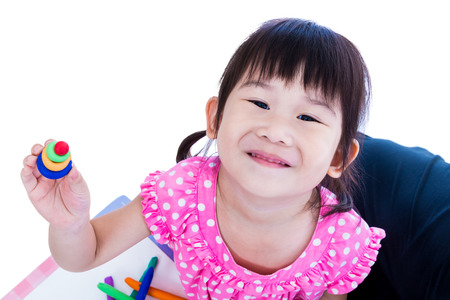 strengthen: Little asian girl playing and creating toys from play dough. Child smiling and show her works from clay, over white background. Strengthen the imagination of child