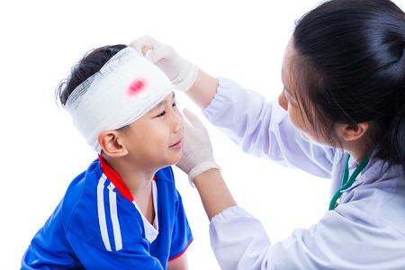 cabeza: Lesion deportiva. Atleta poco asiático niño (tailandés) en ropa deportiva de color azul con un traumatismo de la cabeza llorando, con sangre en el vendaje. El doctor hace una venda en la cabeza del paciente, sobre fondo blanco. Lanzamiento del estudio. Vista lateral. Foto de archivo
