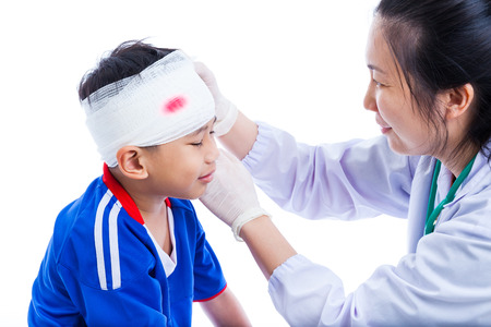 Sports injury. Athlete little asian (thai) boy in blue sportswear with trauma of the head, bloody on bandage crying. Doctor makes bandage on head patient, on white background. Studio shoot. Side view.