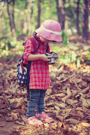 pursuing: Asian girl checking and reviewing photos in professional digital camera over nature background. Active lifestyle, curiosity, pursuing a hobby, technology and kids concept. Retro style. Full body. Stock Photo